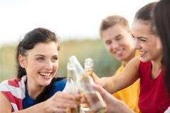 Femmes et hommes avec des boissons sur la plage Photos libres de droits