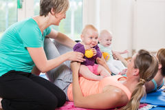 Femmes et leurs bébés dans le cours gymnastique de mère-enfant Images stock