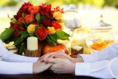 Femmes et mains des hommes avec des anneaux de mariage à une table décorée Photos libres de droits