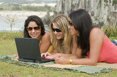 Femmes et ordinateur portatif sur la plage Photo stock