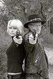 Femmes et pistolets orientants dos à dos d'homme Images stock