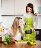 Femmes faisant cuire dans la casserole à la cuisine Image libre de droits