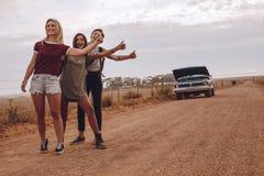 Femmes faisant de l'auto-stop près de leur voiture cassée sur la route de campagne Photos stock