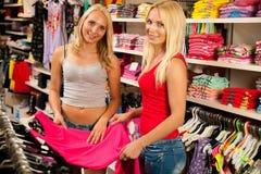 Femmes faisant des emplettes dans un magasin d'habillement Photos libres de droits