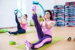 Femmes faisant des exercices réchauffant la jambe étirant la séance d'entraînement photographie stock