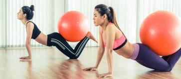 Femmes faisant l'exercice avec la boule d'ajustement dans la classe de gymnase Image stock