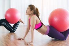 Femmes faisant l'exercice avec la boule d'ajustement dans la classe de gymnase Photographie stock