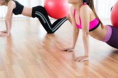 Femmes faisant l'exercice avec la boule d'ajustement dans la classe de gymnase Photo stock