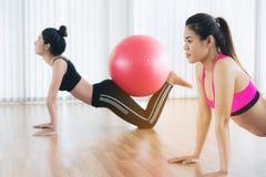 Femmes faisant l'exercice avec la boule d'ajustement dans la classe de gymnase Image libre de droits