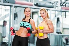 Femmes faisant la séance d'entraînement avec des barbells photos stock