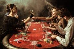 Femmes faisant tinter des boissons tout en jouant le tisonnier dans le casino Photographie stock libre de droits