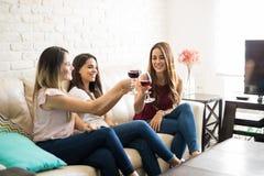 Femmes faisant un pain grillé avec du vin Image libre de droits
