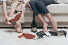 Femmes fatiguées buvant du champagne tout en se reposant sur le sofa à la maison Photos stock