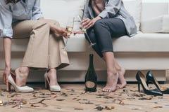 Femmes fatiguées buvant du champagne tout en se reposant sur le sofa à la maison Image libre de droits
