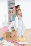 Femmes feignant pour chanter avec des paniers et des vêtements sur le plancher Photo stock