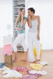Femmes feignant pour chanter avec des paniers et des vêtements sur le plancher Photographie stock