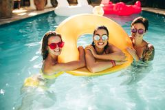 Femmes gaies dans la piscine avec l'anneau gonflable Photos libres de droits