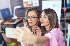 Femmes gaies de sourire d'affaires prenant un selfie dans le bureau Image stock
