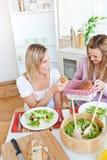 Femmes gaies mangeant de la salade et du pain pendant le déjeuner Images stock