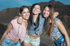 Femmes gaies posant à l'appareil-photo sur la plage Photo libre de droits