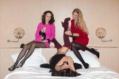 Femmes gaies se trouvant et buvant du champagne Photographie stock libre de droits
