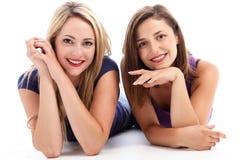 Femmes gais détendant sur l'étage Photo stock