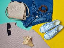 Femmes habillement, chaussures et accessoires sur un fond en pastel jaune bleu Regard à la mode Espadrilles, chandail, jeans, sac Photo stock