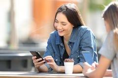 Femmes heureuses à l'aide des téléphones intelligents dans un parc images libres de droits