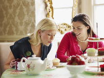 Femmes heureuses à la table de salle à manger Photo stock