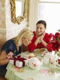 Femmes heureuses à la table de salle à manger Photos stock