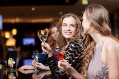 Femmes heureuses avec des boissons à la boîte de nuit Photographie stock libre de droits
