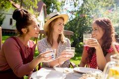 Femmes heureuses avec des boissons à la réception en plein air d'été Photographie stock