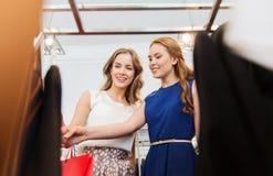 Femmes heureuses avec des paniers à la boutique d'habillement Photographie stock