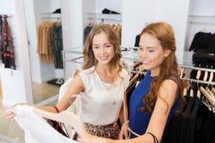 Femmes heureuses avec des paniers à la boutique d'habillement Photo stock