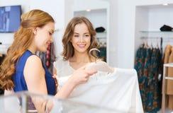 Femmes heureuses avec des paniers à la boutique d'habillement Photos stock