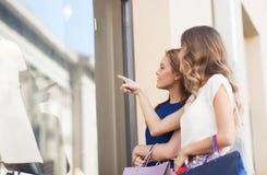 Femmes heureuses avec des paniers à la fenêtre de boutique Photo stock