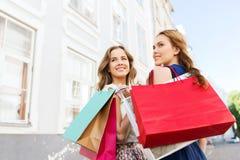 Femmes heureuses avec des paniers marchant dans la ville Images stock