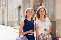 Femmes heureuses avec des paniers marchant dans la ville Image stock