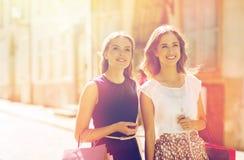 Femmes heureuses avec des paniers marchant dans la ville Photo stock