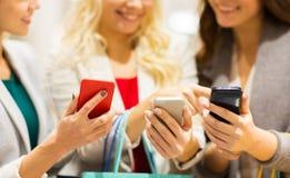 Femmes heureuses avec des smartphones et des paniers Images stock