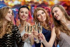 Femmes heureuses avec des verres de champagne au-dessus des lumières Image stock