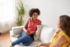 Femmes heureuses avec la maison parlante de gat de boissons Photographie stock
