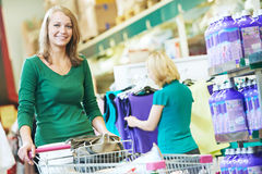Femme avec le caddie au supermarché Photographie stock libre de droits
