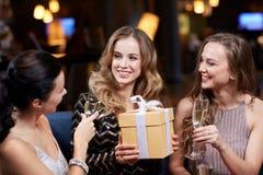 Femmes heureuses avec le champagne et le cadeau à la boîte de nuit Image libre de droits