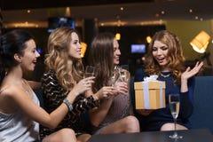Femmes heureuses avec le champagne et le cadeau à la boîte de nuit Photo stock