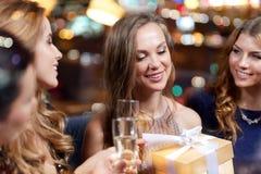 Femmes heureuses avec le champagne et le cadeau à la boîte de nuit Photographie stock