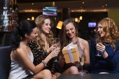 Femmes heureuses avec le champagne et le cadeau à la boîte de nuit Photo libre de droits