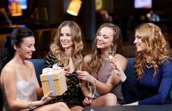 Femmes heureuses avec le champagne et le cadeau à la boîte de nuit Images stock