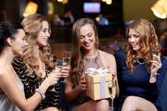 Femmes heureuses avec le champagne et le cadeau à la boîte de nuit Images libres de droits