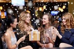 Femmes heureuses avec le champagne et le cadeau à la boîte de nuit Image stock